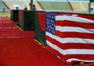 Coffins bearing the bodies of victims of the attack on the Holey Artisan Bakery – one draped in both the Bangladesh and U.S. flags – are laid out for people to pay their last respects, at a stadium in Dhaka, Bangladesh.