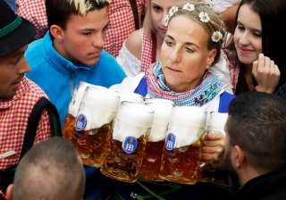 A waitress carries beer mugs during the opening of the 183rd Oktoberfest beer festival in Munich.