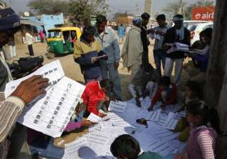 Indians check their names and polling counter on sheets of voters'list outside a polling booth in New Delhi.
