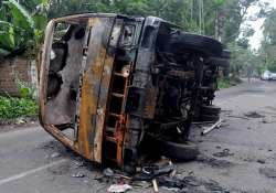 A burnt vehicle seen at a road after a communal riot at- India Tv