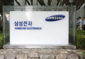 employees walk by the Seoul office of Samsung Electronics- India Tv