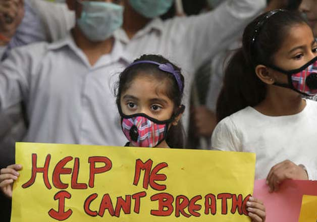 An Indian girls holds a banner during a protest against air pollution in New Delhi, India, Sunday, Nov. 6, 2016. The Delhi government has ordered that all city schools be shut, construction activity halted and all roads be doused with water as crippling air pollution has engulfed the Indian capital. The city, one of the world's dirtiest, has seen the levels of PM2.5 soar to over 900 microgram per cubic meter on Saturday, more than 90 times the level considered safe by the World Health Organization and 15 times the Indian government's norms.