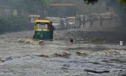 Vehicles wade across a waterlogged street after monsoon