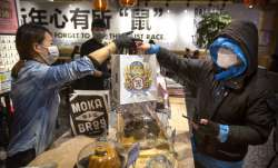 Manager Chen Tiantian, left, hands a takeaway order to a