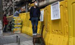 A resident wearing a mask to protect against the spread of the coronavirus looks over barriers used