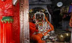 A priest perform religious rituals at Hanuman Garhi temple