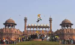 Farmers hoist flags at the Red Fort during the tractor
