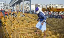 A farmer walks over the police barricades set up on a road at Akshardham to stop farmers during thei