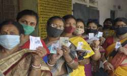 Women show their voter ID card, as they stand in a queue to