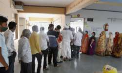 Voters stand in a queue to cast their votes during