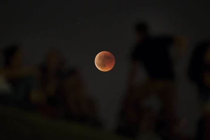 People watch from atop a hill a red moon during a complete